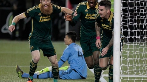 FILE - In this Nov. 22, 2015, file photo, Portland Timbers defender Nat Borchers (7), left, forward Fanendo Adi and defender Liam Ridgewell, right, celebrate Ridgewell's goal during the first half of the first leg of the MLS soccer Western Conference championship against FC Dallas, in Portland, Ore. After retiring last season, three players stayed with the Portland Timbers in another capacity. Former captain Jack Jewsbury is now Portland's director of business development, while fellow midfielder Ned Grabavoy was named director of scouting and recruitment. Defender Nat Borchers _ who spent most of his career in Salt Lake _ joined the Timbers' broadcast team. (AP Photo/Steve Dipaola, File)