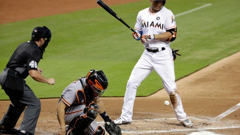 Miami Marlins' Giancarlo Stanton, right, is hit by a pitch thrown by San Francisco Giants starting pitcher Matt Cain during the second inning of a baseball game, Wednesday, Aug. 16, 2017, in Miami. At left is home plate umpire Nick Mahrley (48) and center, San Francisco Giants catcher Nick Hundley. (AP Photo/Lynne Sladky)