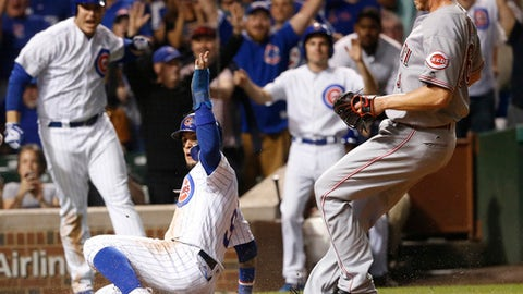 Chicago Cubs' Javier Baez, front left, celebrates scoring the game-winning run on a wild pitch from Cincinnati Reds' Blake Wood, right, during the ninth inning of a baseball game Wednesday, Aug. 16, 2017, in Chicago. The Cubs won 7-6. (AP Photo/Charles Rex Arbogast)