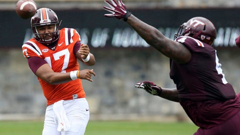 FILE - In this April 22, 2017, file photo, Virginia Tech quarterback Josh Jackson (17) has his pass rushed by defensive lineman Tim Settle (4) during an NCAA college football spring game in Blacksburg, Va. Virginia Tech coach Justin Fuente announced Monday, Aug. 14, 2017 that Jackson will start the Hokies' Sept. 3 season opener against West Virginia.(Matt Gentry/The Roanoke Times via AP, File)