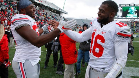 FILE - In this Nov. 19, 2016, file photo, Ohio State's J.T. Barrett, right, and Tyquan Lewis celebrate following a 17-16 win over Michigan State in an NCAA college football game,in East Lansing, Mich. The old guys club at Ohio State this year is exclusive.  Led by quarterback J.T. Barrett, seven players are in their fifth year of eligibility in Columbus _ meaning each had a redshirt year _ and all are not only at the top of the Buckeyes' depth chart, they're among the best players in college football.  (AP Photo/Al Goldis, File)