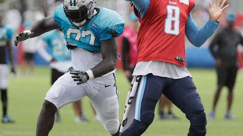Tennessee Titans quarterback Marcus Mariota (8) passes as he is rushed by Carolina Panthers defensive end Mario Addison (97) during a combined NFL football training camp Thursday, Aug. 17, 2017, in Nashville, Tenn. (AP Photo/Mark Humphrey)
