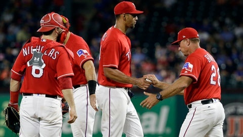 Texas Rangers catcher Brett Nicholas (6) watches as starting pitcher Tyson Ross, center, turns the ball over to manager Jeff Banister, right, during the fifth inning of a baseball game against the Chicago White Sox on Thursday, Aug. 17, 2017, in Arlington, Texas. (AP Photo/Tony Gutierrez)