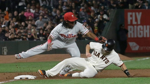 Philadelphia Phillies third baseman Maikel Franco, top, tags out San Francisco Giants' Buster Posey during the fifth inning of a baseball game in San Francisco, Thursday, Aug. 17, 2017. (AP Photo/Jeff Chiu)