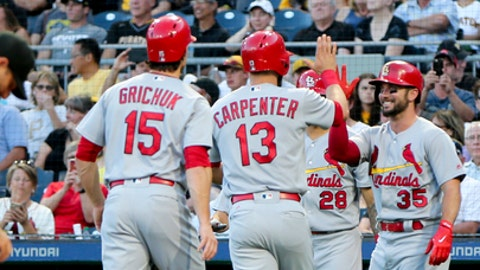 Fans cheere as St. Louis Cardinals' Matt Carpenter (13) is greeted by teammates Randal Grichuk (15), Greg Garcia (35) at home plate after hitting a three-run home run against the Pittsburgh Pirates in the second inning of a baseball game, Friday, Aug. 18, 2017, in Pittsburgh. (AP Photo/Keith Srakocic)