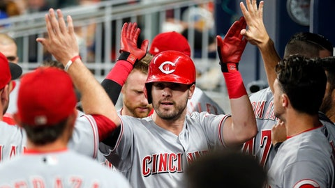 Cincinnati Reds' Jesse Winker, center, celebrates in the dugout after hitting a home run during the sixth inning of a baseball game against the Atlanta Braves on Friday, Aug. 18, 2017, in Atlanta. The Reds hit three homers in the inning. (AP Photo/John Bazemore)