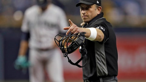Home plate umpire Chris Guccione points to Tampa Bay Rays' Kevin Kiermaier during the first inning of a baseball game Saturday, Aug. 19, 2017, in St. Petersburg, Fla. The World Umpires Association, the union representing Major League Baseball umpires, announced that umpires will be wearing white wristbands during all games to protest the escalating verbal attacks on umpires and their strong objection to the Office of the Commissioner's response to the verbal attacks. (AP Photo/Chris O'Meara)