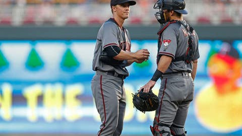Arizona Diamondbacks pitcher Zack Greinke, left, gets a visit from catcher Jeff Mathis after he gave up the second of two walks to the Minnesota Twins to load the bases during the first inning of a baseball game Saturday, Aug. 19, 2017, in Minneapolis. (AP Photo/Jim Mone)