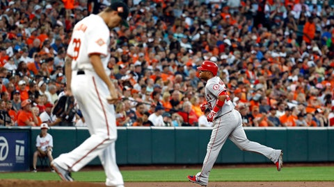 Los Angeles Angels' Luis Valbuena, right, rounds the bases past Baltimore Orioles starting pitcher Kevin Gausman after hitting a solo home run in the second inning of a baseball game in Baltimore, Saturday, Aug. 19, 2017. (AP Photo/Patrick Semansky)
