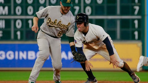 Houston Astros' Jose Altuve, right, sticks out his tongue as he is caught stealing base on a tag by Oakland Athletics second baseman Jed Lowrie in the eighth inning of a baseball game Saturday, Aug. 29, 2017, in Houston. (AP Photo/Richard Carson)