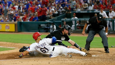 Texas Rangers' Robinson Chirinos is tagged out at the plate by Chicago White Sox catcher Kevan Smith while home plate umpire Tim Timmons, right, watches during the fourth inning of a baseball game, Saturday Aug. 19, 2017, in Arlington, Texas. (AP Photo/Roger Steinman)