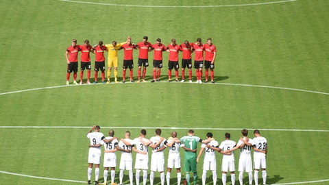The two teams stand for a minute of silence in memory of those killed in the recent terror attack in Barcelona ahead of the German Bundesliga soccer match between SC Freiburg and Eintracht Frankfurt in the Black Forest Stadium in Freiburg, Germany, Sunday, Aug. 20, 2017.  (Patrick Seeger/dpa via AP)