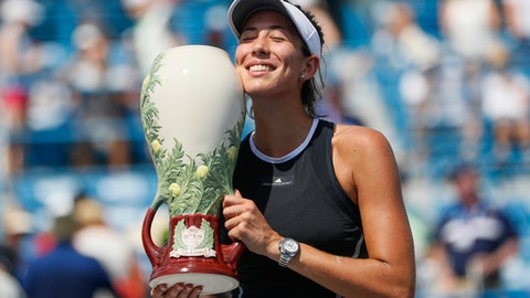 Garbine Muguruza, of Spain, holds the Rookwood Cup after defeating Simona Halep, of Romania, in the women's singles final at the Western & Southern Open, Sunday, Aug. 20, 2017, in Mason, Ohio. Muguruza won 6-1, 6-0. (AP Photo/John Minchillo)