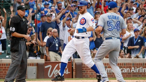 Chicago Cubs' Ben Zobrist, center, scores on a game winning single hit by Alex Avila off Toronto Blue Jays' Roberto Osuna during the tenth inning of a baseball game, Sunday, Aug. 20, 2017, in Chicago. (AP Photo/Kamil Krzaczynski)