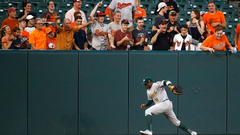 Oakland Athletics left fielder Rajai Davis chases after a fly ball single that was hit by Baltimore Orioles' Chris Davis in the second inning of a baseball game in Baltimore, Monday, Aug. 21, 2017. (AP Photo/Patrick Semansky)