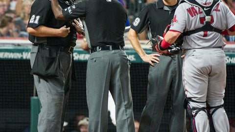 Umpire Hunter Wendelstedt, left, talks with umpire Alan Porter as umpire Andy Fletcher and Cleveland Indians' Roberto Perez watch during the sixth inning of a baseball game against the Boston Red Sox in Cleveland, Monday Aug. 21, 2017. Wendelstedt finished the inning but left the game. (AP Photo/Phil Long)