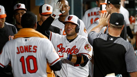 Baltimore Orioles' Welington Castillo, center, high-fives teammates in the dugout after hitting a solo home run in the eighth inning of a baseball game against the Oakland Athletics in Baltimore, Monday, Aug. 21, 2017. Baltimore won 7-3. (AP Photo/Patrick Semansky)