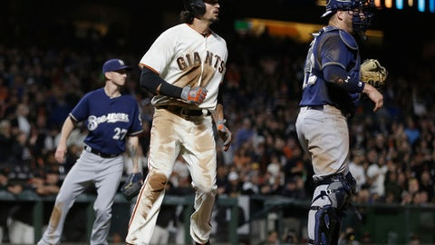 San Francisco Giants' Jarrett Parker, center, scores on a double by Brandon Crawford in the fourth inning of a baseball game against the Milwaukee Brewers Monday, Aug. 21, 2017, in San Francisco. At left is Brewers pitcher Zach Davies, at right catcher Stephen Vogt. (AP Photo/Ben Margot)