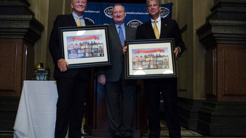 Philadelphia Mayor Jim Kenney, center, presents West Point athletic director Boo Corrigan, left, and Navy athletic director Chet Gladchuk, right, with a gift, Tuesday, Aug. 22, 2017, in Philadelphia. The Army-Navy football game will be played in Philadelphia four times from 2018-2022, returning to its most frequent host city. The academies announced Tuesday at Philadelphia's City Hall that Lincoln Financial Field, home of the NFL's Eagles, will be the site of the 2018, '19, '20 and '22 Army-Navy games.(Joy Lee/The Philadelphia Inquirer via AP)