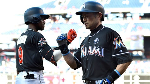 Miami Marlins' Ichiro Suzuki, right, is congratulated by Dee Gordon after Suzuki hit a three-run home run off Philadelphia Phillies' Aaron Nola during the seventh inning of the first baseball game in a doubleheader, Tuesday, Aug. 22, 2017, in Philadelphia. (AP Photo/Derik Hamilton)