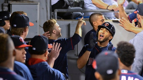 Minnesota Twins' Eddie Rosario, right, celebrates in the dugout after he hit a two-run home run against the Chicago White Sox during the sixth inning of a baseball game in Chicago on Tuesday, Aug. 22, 2017. (AP Photo/Matt Marton)