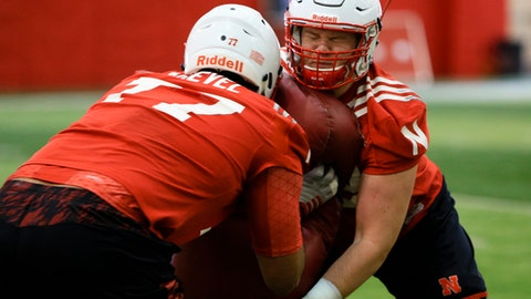 FILE- In this March 8, 2016, file photo, Nebraska offensive lineman David Knevel (77) and offensive lineman Cole Conrad (62) go through a drill during NCAA college football spring practice in Lincoln, Neb. Nebraska's Cole Conrad has made the journey from small-school football star with no scholarship offers to starting center in the Big Ten. Conrad appeared in all 13 games last season at right tackle and started the last five. The junior moved to center in the spring and was awarded a scholarship. Last week he found out he had won the starter's job for the opener against Arkansas State next week. (AP Photo/Nati Harnik, File)