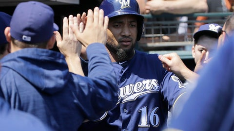 Milwaukee Brewers' Domingo Santana, center, is congratulated after scoring against the San Francisco Giants during the first inning of a baseball game in San Francisco, Wednesday, Aug. 23, 2017. (AP Photo/Jeff Chiu)