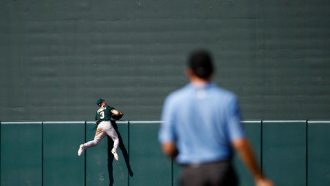 Oakland Athletics center fielder Boog Powell (3) and first base umpire John Tumpane watch a three-run home run ball that was hit by Baltimore Orioles' Trey Mancini in the fourth inning of a baseball game in Baltimore, Wednesday, Aug. 23, 2017. (AP Photo/Patrick Semansky)