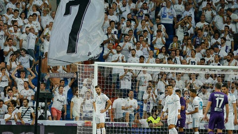 Real Madrid's Cristiano Ronaldo, 2nd left waits for a corner kick as fans wave a giant number 7 flag, Ronaldo's shirt number, during the Santiago Bernabeu Trophy soccer match between Real Madrid and Fiorentina at the Santiago Bernabeu stadium in Madrid, Spain, Wednesday, Aug. 23, 2017. (AP Photo/Paul White)