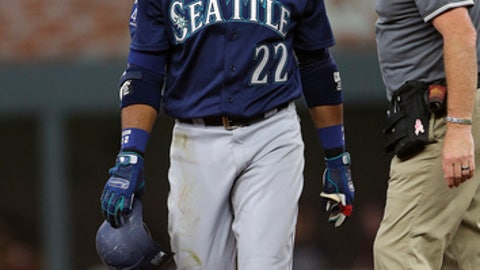 Seattle Mariners second baseman Robinson Cano (22) walks off the field with a member of the training staff after being injured in the second inning of a baseball game against the Atlanta Braves Wednesday, Aug. 23, 2017, in Atlanta. (AP Photo/John Bazemore)