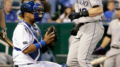 Colorado Rockies' Charlie Blackmon crosses the plate past Kansas City Royals catcher Salvador Perez after hitting a solo home run during the third inning of a baseball game Wednesday, Aug. 23, 2017, in Kansas City, Mo. (AP Photo/Charlie Riedel)