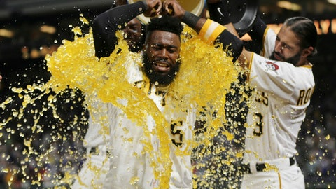 Pittsburgh Pirates' Josh Harrison (5) has a bucket of sports drink and ice dumped over his head by teammates Sean Rodriguez (3) and Josh Bell, left, as he is interviewed after hitting a walk-off home run to beat the Los Angeles Dodgers and break up the no-hitter by Dodgers starting pitcher Rich Hill in the tenth inning of a baseball game, Wednesday, Aug. 23, 2017, in Pittsburgh. The Pirates won 1-0 in ten innings.(AP Photo/Keith Srakocic)