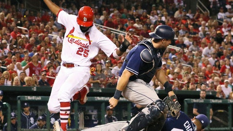 St. Louis Cardinals' Dexter Fowler scores on a wild pitch by San Diego Padres pitcher Jhoulys Chacin, right, as catcher Austin Hedges looks for the ball during the fifth inning of a baseball game Wednesday, Aug. 23, 2017, in St. Louis. Fowler made contact with Chacin's foot as he crossed the plate and Chacin was tended to by a trainer before remaining in the game. (Chris Lee/St. Louis Post-Dispatch via AP)