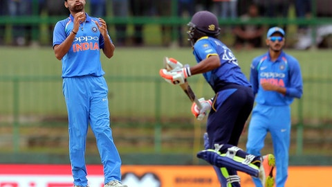 India's Bhuvneshwar Kumar, left, reacts after bowling a delivery to Sri Lanka's Niroshan Dickwella, center, during their second one-day international cricket match in Pallekele, Sri Lanka, Thursday, Aug. 24, 2017. (AP Photo/Eranga Jayawardena)