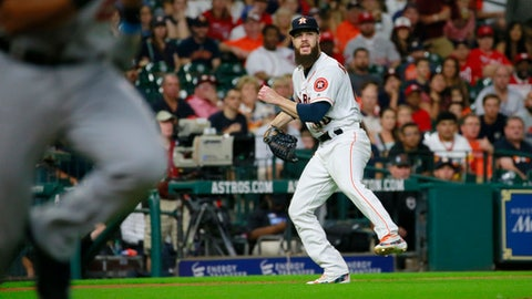Houston Astros' pitcher Dallas Keuchel watches his throw on a ball hit by Washington Nationals' Pedro Severino for a single during the fifth inning of a baseball game Thursday, Aug. 24, 2017, in Houston. (AP Photo/Richard Carson)