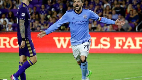 FILE - In this Sunday, May 21, 2017 file photo, New York City FC's David Villa celebrates his goal as he runs past Orlando City's Leo Pereira, left, in an MLS soccer game in Orlando, Fla. David Villa has been called up by Spain for the first time since the 2014 World Cup, giving the country's record scorer a chance to add to his 59 international goals. (AP Photo/John Raoux, File)