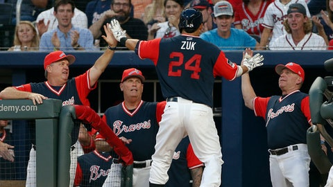Atlanta Braves catcher Kurt Suzuki (24) is greeted at the dugout after hitting a solo home run during the second inning of a baseball game against the Colorado Rockies on Friday, Aug. 25, 2017, in Atlanta. (AP Photo/John Bazemore)