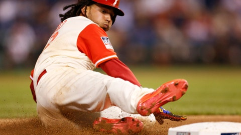 Philadelphia Phillies' Freddy Galvis slides safely to third base on a throwing error by Chicago Cubs catcher Alex Avila, as Galvis had stolen second, during the fourth inning of a baseball game, Friday, Aug. 25, 2017, in Philadelphia. (AP Photo/Laurence Kesterson)