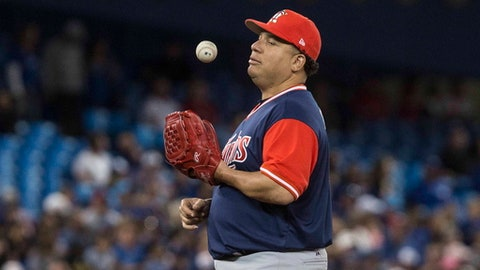 Minnesota Twins pitcher Bartolo Colon tosses the baseball in the air as he waits to be pulled from the game by manager Paul Molitor during the seventh inning against the Toronto Blue Jays on Friday, Aug. 25, 2017, in Toronto. (Chris Young/The Canadian Press via AP)