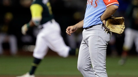 Texas Rangers pitcher Nick Martinez, right, waits for Oakland Athletics' Khris Davis to run the bases on a home run during the seventh inning of a baseball game Friday, Aug. 25, 2017, in Oakland, Calif. (AP Photo/Ben Margot)