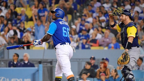 Los Angeles Dodgers' Yasiel Puig, left, heads to first as he hits a solo home run while Milwaukee Brewers catcher Stephen Vogt watches during the sixth inning of a baseball game, Friday, Aug. 25, 2017, in Los Angeles. (AP Photo/Mark J. Terrill)