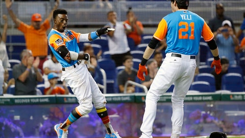 Miami Marlins' Dee Gordon, left, celebrates with Christian Yelich (21) after Gordon scored on a double by Giancarlo Stanton during the third inning of a baseball game against the San Diego Padres, Sunday, Aug. 27, 2017, in Miami. (AP Photo/Wilfredo Lee)