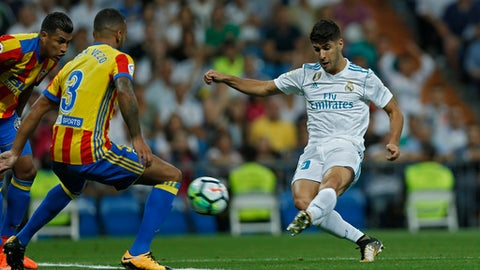 Real Madrid's Marco Asensio, right, scores the opening goal past Valencia's Ruben Vezo during a Spanish La Liga soccer match between Real Madrid and Valencia at the Santiago Bernabeu stadium in Madrid, Sunday, Aug. 27, 2017. (AP Photo/Francisco Seco)