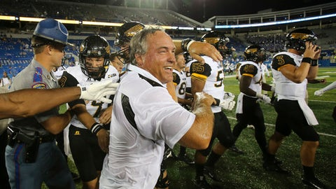 FILE - In this Sept. 3, 2016, file photo, Southern Mississippi head coach Jay Hopson, center, celebrates with his team after defeating Kentucky in an NCAA college football game, in Lexington, Ky. Southern Miss rallied for a stunning 44-35 win over Kentucky last year in Lexington. Now the Golden Eagles get a chance to make it two in a row _ and this time the game's at home in Roberts Stadium.(AP Photo/David Stephenson, File)