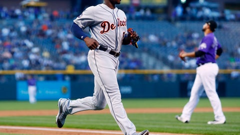 Detroit Tigers' Justin Upton, front, scores on a single hit by Nicholas Castellanos as Colorado Rockies starting pitcher Antonio Senzatela reacts in the background in the first inning of a baseball game Monday, Aug. 28, 2017, in Denver. (AP Photo/David Zalubowski)