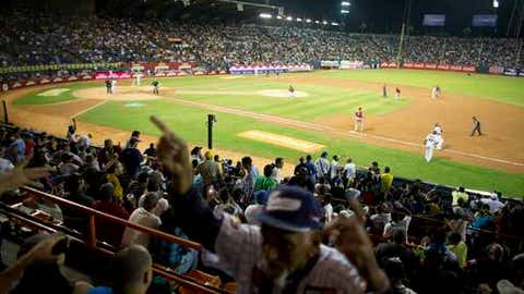 FILE - In this Oct. 27, 2015 file photo, fans watch a baseball game between the Leones de Caracas and the Navegantes del Magallanes, in Caracas. Venezuela's baseball stadiums for years served as a sporting sanctuary where fans of all backgrounds gathered to watch some of the nation's top major league players and forget about their mounting hardships. But some are beginning to wonder whether it's time to at least temporarily hang up the nation's pastime as the country's crisis deepens to unprecedented levels. (AP Photo/Ariana Cubillos, File)