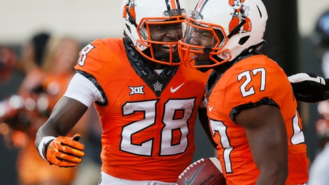 Oklahoma State running back J.D. King (27) celebrates a touchdown with teammate James Washington (28) during the first half of an NCAA college football game against Tulsa in Stillwater, Okla., Thursday, Aug. 31, 2017. (AP Photo/Sue Ogrocki)
