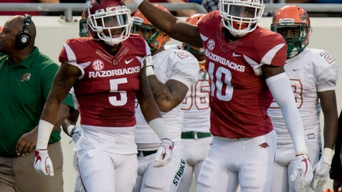 Arkansas defensive back Henre' Toliver, 5, and linebacker Randy Ramsey, 10, celebrate after a broken up pass during the second quarter of an NCAA college football game against Florida A&M on Thursday, Aug. 31, 2017, in Little Rock, Ark.. (AP Photo/Gareth Patterson)