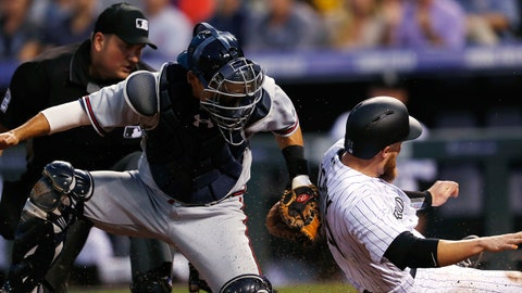 Colorado Rockies' Jonathan Lucroy, right, slides safely across home plate to score as Atlanta Braves catcher Kurt Suzuki applies the tag during the third inning of a baseball game Wednesday, Aug. 16, 2017, in Denver. The Rockies won 17-2. (AP Photo/David Zalubowski)