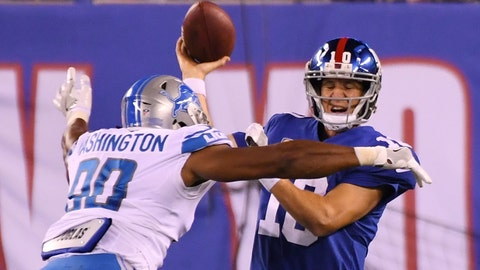Sep 18, 2017; East Rutherford, NJ, USA; New York Giants quarterback Eli Manning (10) is pressured by Detroit Lions defensive end Cornelius Washington (90) in the fourth quarter during a NFL football game at MetLife Stadium. Mandatory Credit: Robert Deutsch-USA TODAY Sports